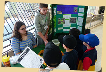 Endangered Species Day kids at their table explaining project to younger guests there for the day.
