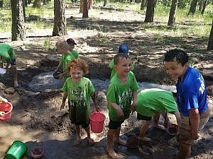 Summer campers kindergarten mud-kitchen fun in the mud outdoors together