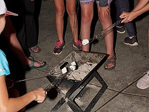Roasting s'mores before an evening tour at the Zoo