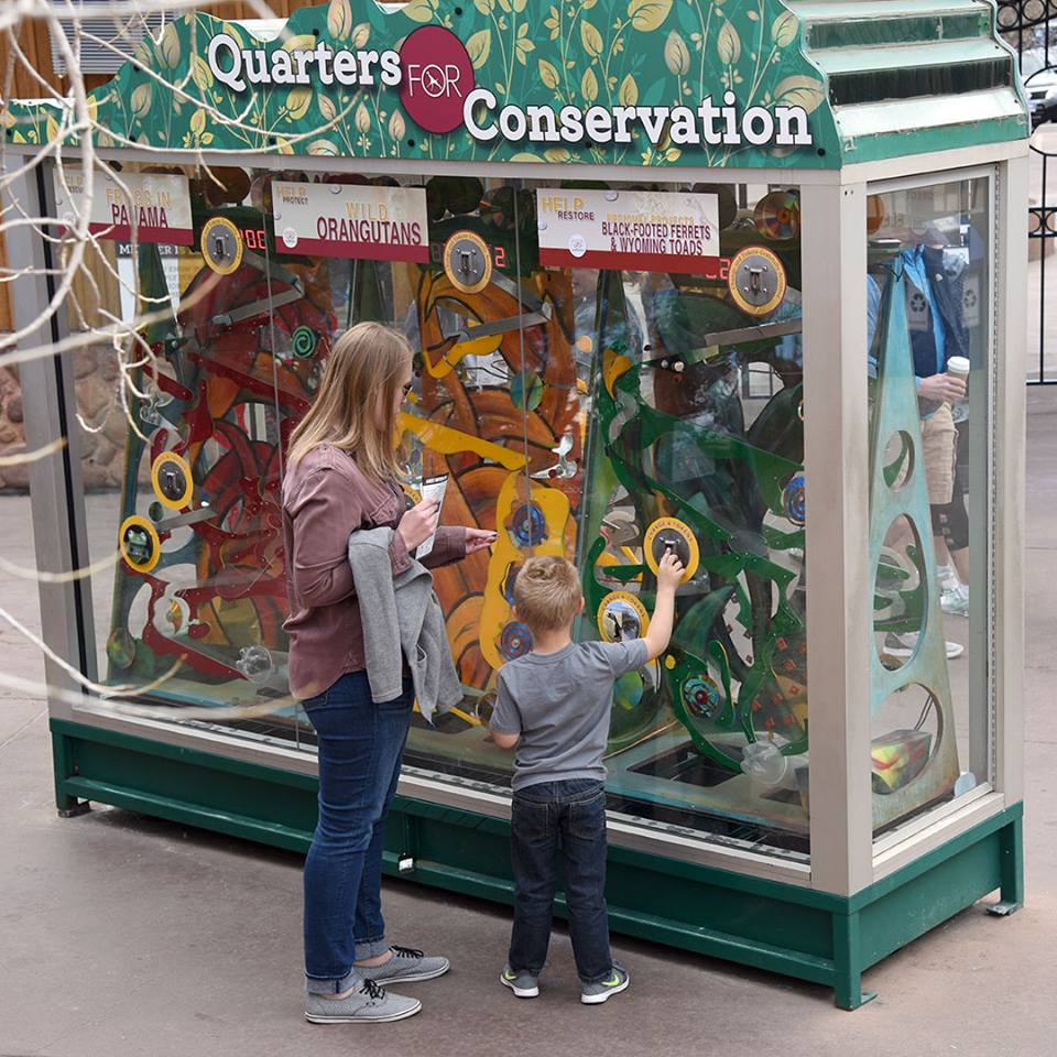 Quarters for Conservation kiosk with mother and child voting using tokens