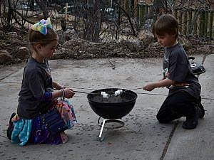 Evening s'more roast with two children holding marshmallows