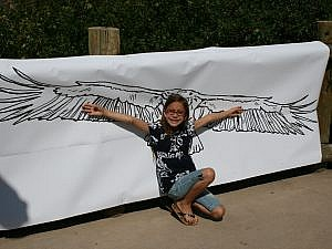 Girl stretching arms to match vulture wings on paper at International Vulture Day activities